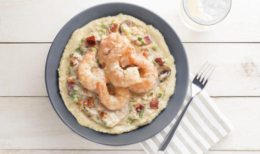 gray plate with grits, shrimp, bacon, mushroom, peppers, onions and ...